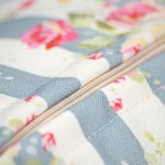 bespoke printed cotton cushion with flowers on with a close up of the zip and lining